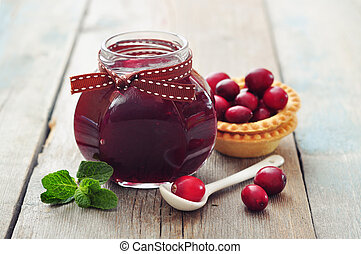 Cranberry jam in glass jar with fresh berry on wooden...