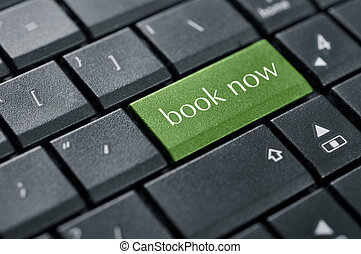 Book now green button on computer keyboard closeup