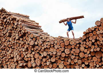 man lifting heavy log - training - man on top of large pile...