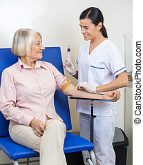 Businesswoman Undergoing Blood Test - Senior businesswoman...
