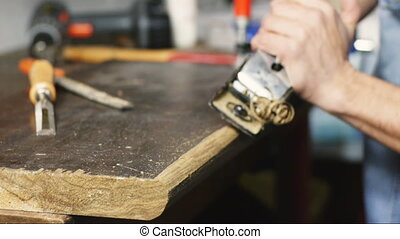 carpenter planing wood plane - joiner in his shop planing a...
