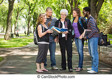 Students Discussing Notes On Campus Road - Full length of...