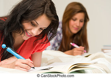 Young teenager girls studying on bed - Young teenage girls...