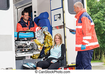 Woman in ambulance with paramedics aid accident