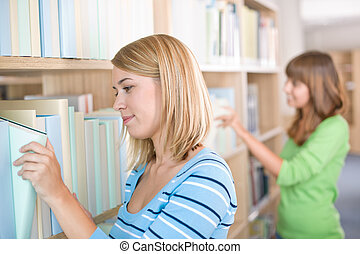 Student in library - two woman search for book in bookshelf