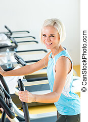 Fitness young woman on elliptical cross trainer at health...