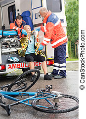 Emergency paramedics helping woman bike accident