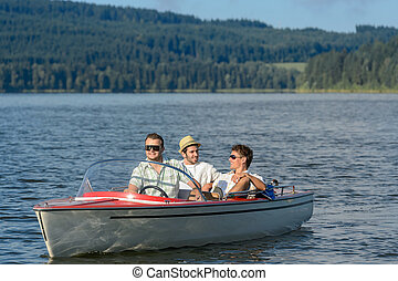 Young men sitting in motorboat scenic landscape - Young men...
