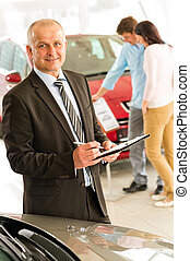 Portrait of salesman working in car dealership - Closeup...