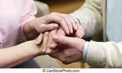 Caring Hands - Close-up of caring seniors holding hands