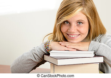 Smiling student teenager leaning head on books - Smiling...