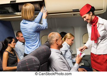 Air stewardess check ticket airplane cabin smiling - Air...