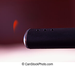 Lighter - Black lighter with lit flame near a candle, close...