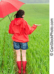 Woman standing in raincoat and with umbrella