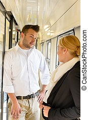 Woman and man talking on train hall colleagues travel...