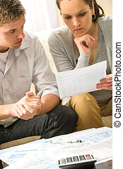 Troubled couple calculating finances