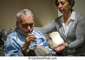 Senior man taking medication with water caring wife helping