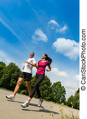 Low angle view of couple running outdoors - Low angle view...
