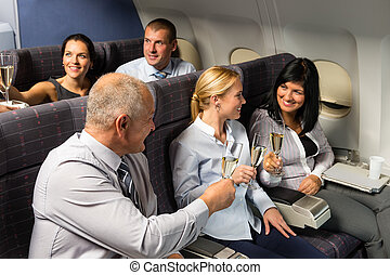 Airplane cabin businesspeople toasting champagne - Airplane...