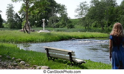 girl bench white grass - fast flowing stream near is located...