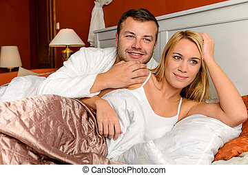 Smiling husband holding wife lying bed married