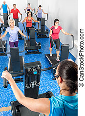 Fitness instructor leading treadmill running class at health...
