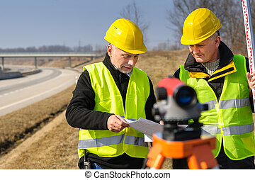 Geodesist two man theodolite stand highway - Two male...