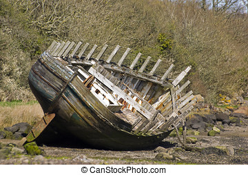 Shipwrecked fishing boat on beach in Anglesey Wales