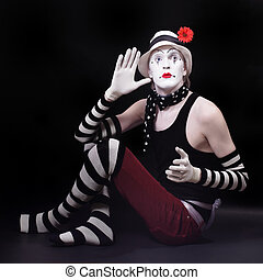 Mime in white hat with red flower sits on the floor -...