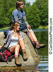 Young trekking couple resting at lakeside on sunny day