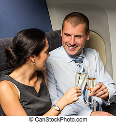 Flight cabin business partners toasting champagne airplane...