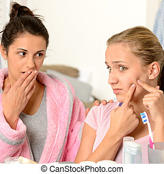 Young teenager and her friend squeeze pimple in the bathroom