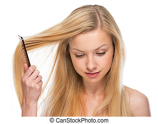 Young woman combing hair