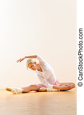 Ballet dancer in leaning posture exercise studio reaching...