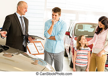 Car dealer offering vehicle to young family - Car dealer...