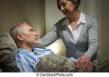 Worried senior woman caring with sick husband in the bedroom