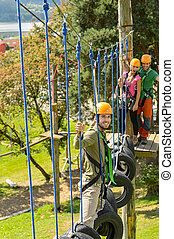 Smiling man climbing in adventure park - Young friends...