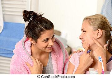 Teenage girls having acne problems in bathroom - Teenage...
