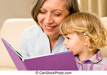 Grandmother and granddaughter read book together -...