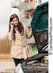 mujer, Mirar, debajo, coche, capucha, teléfono