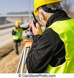 Geodesist measure land with tacheometer highway - Land...