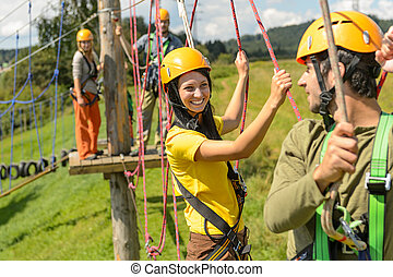 Young couple in safety equipment adventure park - Visitors...