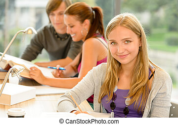 High-school student taking notes in study room smiling...