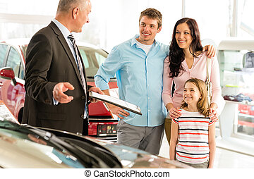 Salesman offering a car to family - Car dealer offering a...