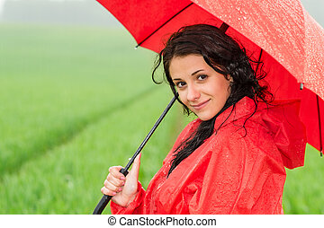Smiling woman looking at camera during rainfall posing with...