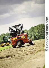 Truck and Delivery - Truck mounted forklift collecting turf...
