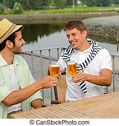 Cheerful male friends drinking beer at pub - Cheerful male...