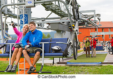 Happy couple traveling chair lift enjoying landscape - Happy...