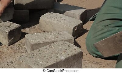 Construction worker cleaning bricks