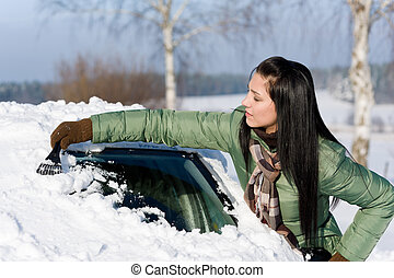 Winter car - woman remove snow from windshield with ice...